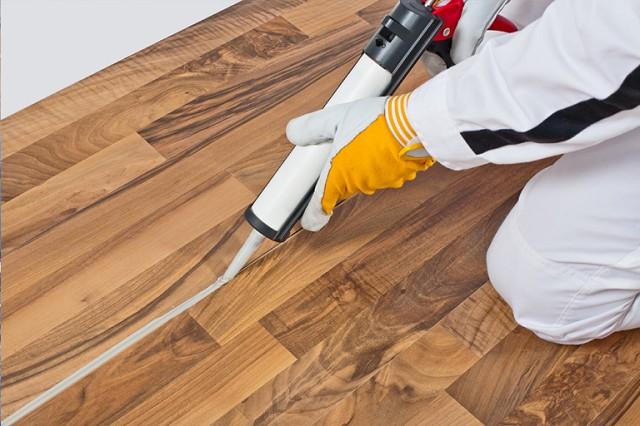 Заполнение щелей герметиком для деревянных полов.